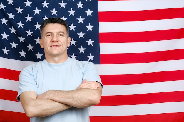 立って、米国旗の背景に笑みを浮かべて、カメラに直接見えるカジュアルな青いtシャツを着た中年の白人アメリカ人の男の肖像画。テキスト用のスペースをコピーする