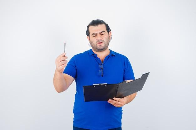 폴로 티셔츠에 연필을 들고 사려 깊은 전면보기를 보면서 클립 보드를 통해보고 중간 세 남자의 초상화