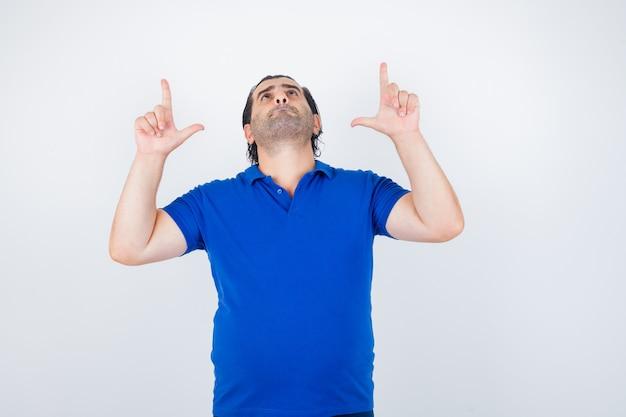 Портрет мужчины средних лет, указывающий вверх в синей футболке и уверенно выглядящий, вид спереди