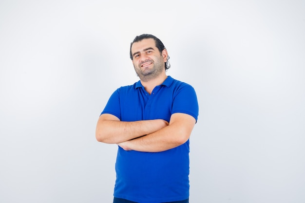 青いtシャツで腕を組んで立って幸せな正面図を探している中年男性の肖像画