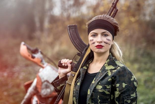 야외에서 소총을 들고 군인 여자의 초상화