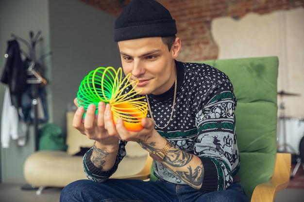 Портрет миллениального мальчика, использующего ретро-игрушки, встречая вещи из прошлого и веселясь