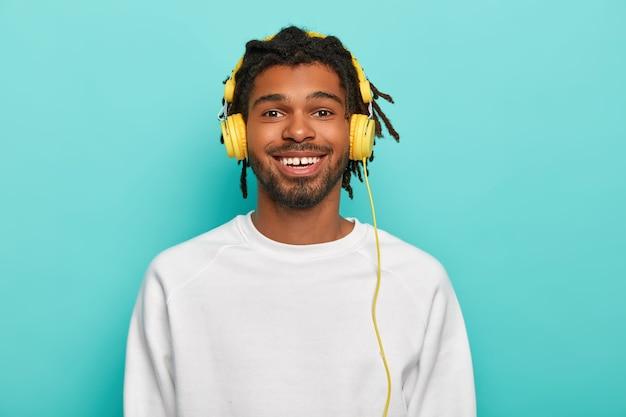 ドレッドヘアを持つ千年紀のメロマンの男の肖像画、黄色のヘッドフォンを着用し、広く笑顔、好きな音楽を楽しんで、白いセーターを着ています
