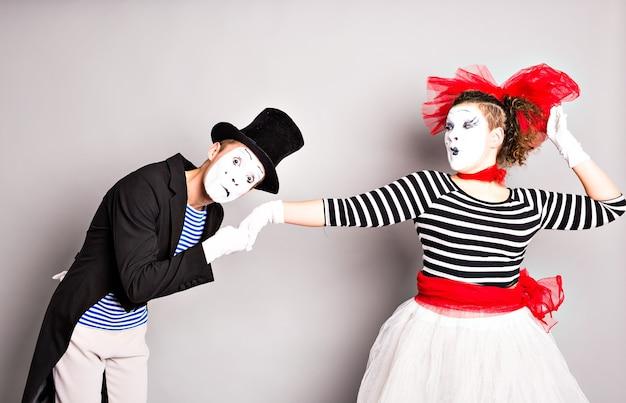 恋をしているパントマイムの肖像画。男性は女性の手にキスします。