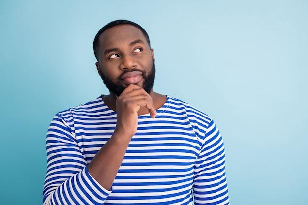 心に焦点を当てたアフリカ系アメリカ人の男の肖像は、思考が決定を決定すると思います春の休日についての選択ソリューションを選択します青い色の壁の上に隔離された航海ベストフロックを着用します