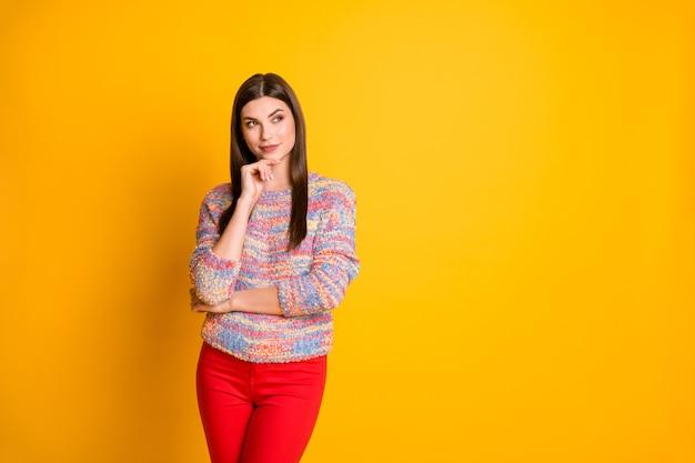 Портрет настроенной заинтересованной девушки думает, мысли ее мечтательные выходные выглядят copyspace касаются подбородка руки носят современный пуловер, изолированный на сияющем цвете