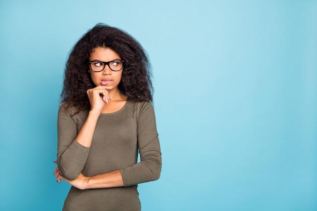 Портрет задумчивой, задумчивой, заинтересованной темнокожей девушки, думающей, что у нее ужасные мысли, чувствовать страх, испуганные эмоции, кусать губы, выглядеть стильно, носить, изолировать на стене синего цвета