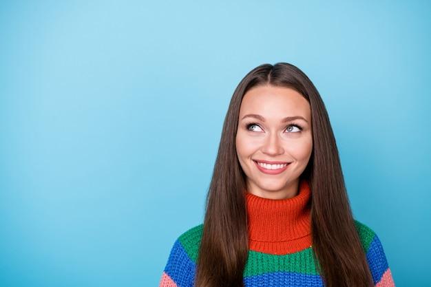 마음이 긍정적인 소녀의 초상화는 카피스페이스 계획을 고려하여 주말 휴일에 파란색 배경 위에 격리된 무지개 스웨터를 입습니다.