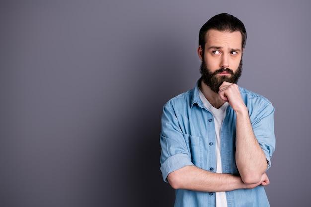 気にされた困惑した焦点を絞った男のフリーランサーの肖像画コピースペースタッチあごの手は考えを発明する仕事のアイデアは灰色の色の壁に隔離されたモダンな服を着ると思います