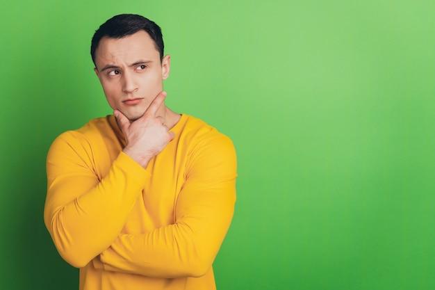 생각이 진지한 불확실한 남자 손가락 턱의 초상화는 녹색 배경에 대해 생각합니다.