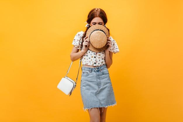 麦わら帽子で顔を覆っているいたずら好きな女の子の肖像画。明るいデニムのスカートとオレンジ色の背景にポーズをとる花柄のトップに身を包んだ女性。