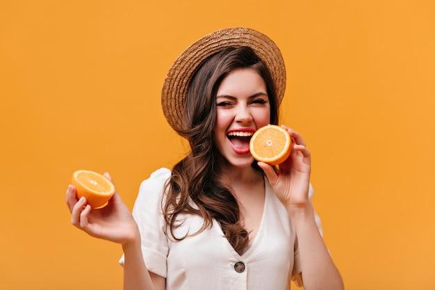 오렌지를 물고 물결 모양의 머리를 가진 장난 여자의 초상화. 오렌지 배경에 포즈 밀 짚 모자에있는 여자.
