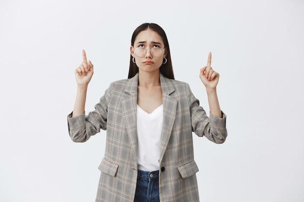 Портрет несчастной расстроенной привлекательной женщины с темными волосами и очками в стильной куртке, дующейся и скулящей, указывая и глядя вверх, мрачная и недовольная