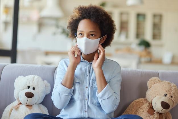 保護フェイスマスクを着用し、脇を見てカジュアルな服を着た混血の十代の少女の肖像画