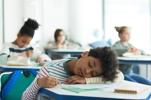 学校の教室、コピースペースの机で寝ている混血の少年の肖像画