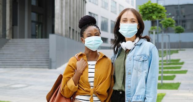 Портрет лучших друзей молодых веселых женщин смешанных рас в медицинских масках, стоя на улице и улыбаясь. студенты многоэтнических счастливых девочек на открытом воздухе. афро-американские и кавказские женщины. пандемия.