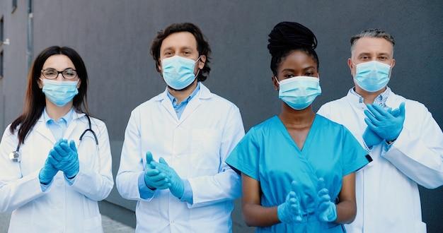 医療用マスク、手袋、白いガウンを着て立って、拍手喝采し、カメラを見ている混血の若い男性と女性の医師の肖像画。多民族の医者。コロナウイルスの概念。拍手。