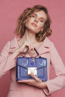 ピンクの青いバッグを保持しているモデルの肖像画。