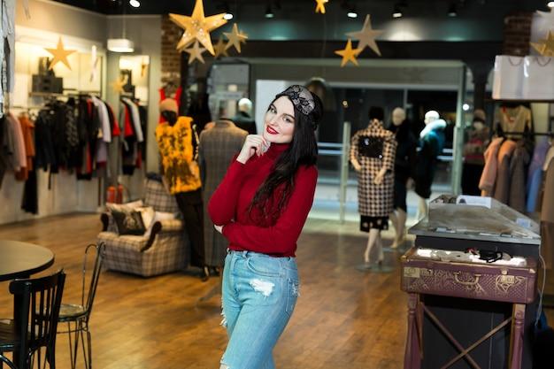 Портрет модельной женщины в спальной маске. довольно молодая женщина, счастливо улыбается и позирует в магазине одежды