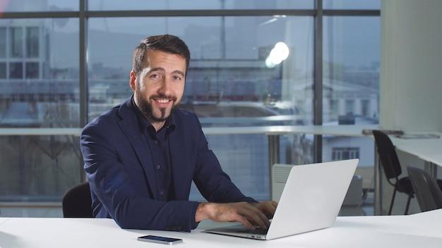 ラップトップを使用してオフィスの机で働く現代の魅力的なビジネスマンの肖像画