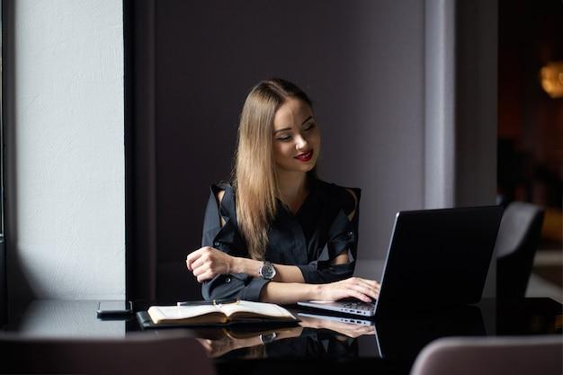 ノートパソコンと日記の職場の上に座って、コンピューターで作業して現代のビジネスの女性の肖像画