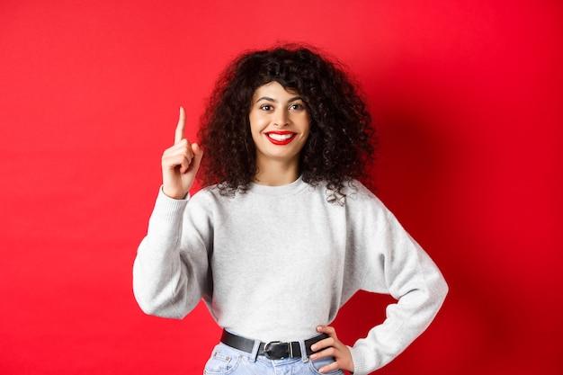 곱슬머리를 가진 현대 유럽 여성의 초상화가 1위를 보여주고, 주문을 하고, 손가락을 들고 웃고, 빨간색 배경에 서 있습니다.
