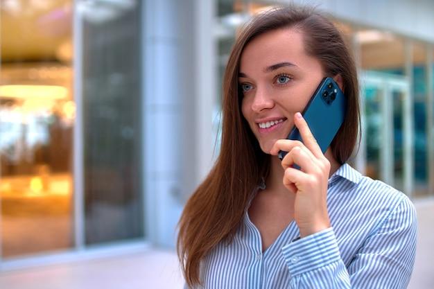現代の幸せなカジュアルな笑顔のスマートミレニアル女性の話電話の肖像画