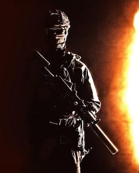 현대 보병 병사의 초상화, 특수 작전 부대 소총수, 헬멧을 쓴 경찰 전술 그룹 전투기, 침묵 서비스 소총으로 무장한 마스크, 하드 사이드 라이트 스튜디오 촬영이 있는 낮은 키