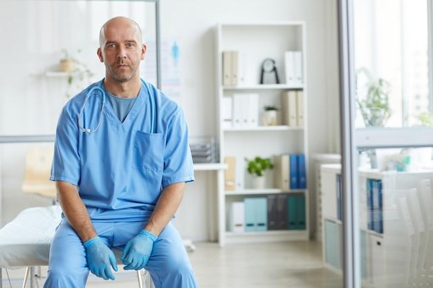 Портрет современного человека в синей форме, работающего в больнице, сидя в своем офисе