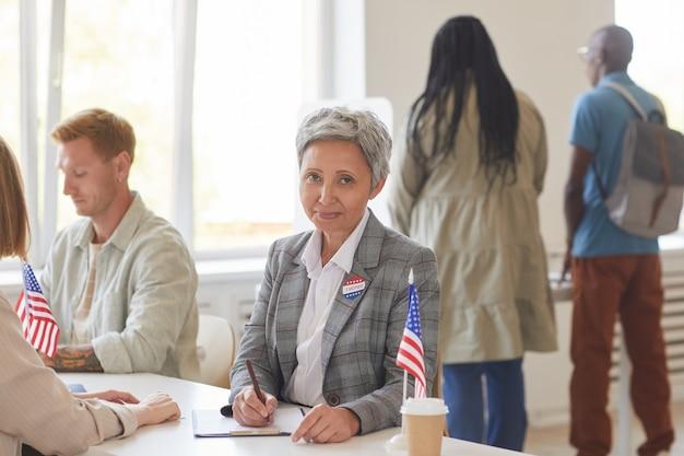 Портрет современной зрелой женщины, регистрирующей избирателей, работая за столом в день выборов, копировальное пространство