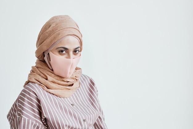 흰 벽에 포즈를 취하는 동안 마스크를 쓰고 카메라를 바라보는 현대 중동 여성의 초상화, 공간 복사