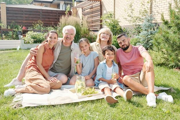 晴れた夏の日に裏庭の芝生でピクニックをしている現代の多世代家族の肖像画