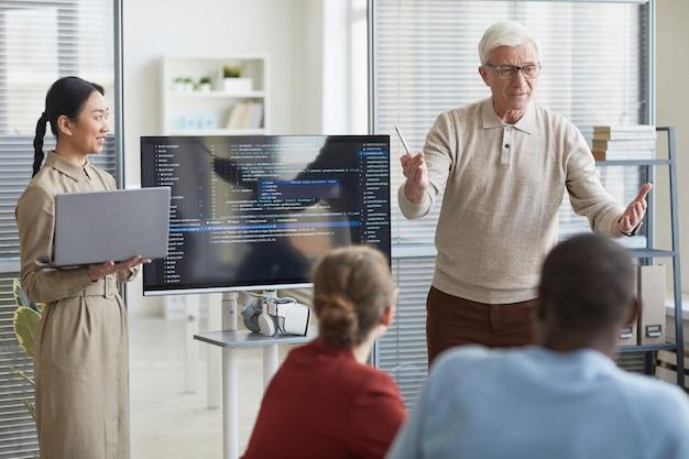画面上のコード、コピースペースでitチームにオフィスでプレゼンテーションを行う現代のシニアビジネスマンの肖像画