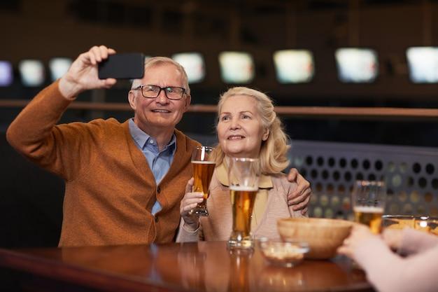 Портрет современной пожилой пары, делающей селфи-фото, попивая пиво в баре и наслаждаясь ночью с друзьями, копией пространства
