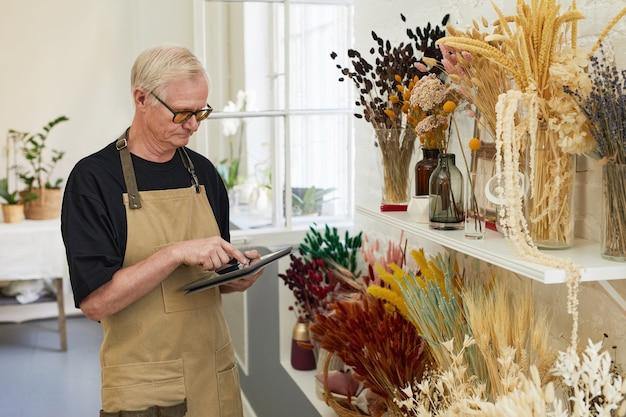 Портрет современного старшего мужчины, занимающегося инвентаризацией запасов, работая в копировальном пространстве магазина флористов