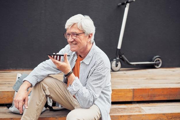 Портрет современного старшего мужчины, использующего смартфон на открытом воздухе во время отдыха в городе с электросамокатом в фоновом режиме