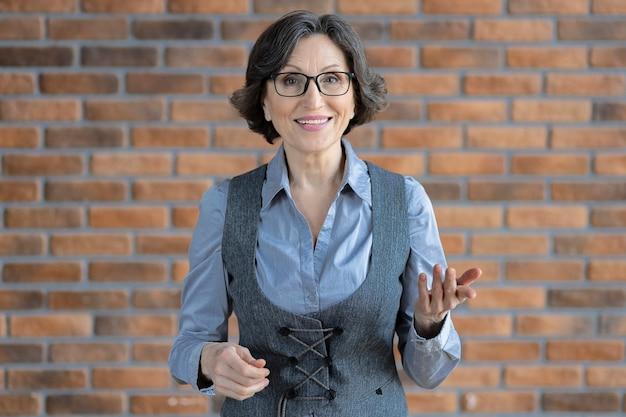 카메라를 보고 화상 통화를 하는 안경을 쓰고 웃고 있는 현대적인 백인 사업가의 초상화. 온라인 회의, 화상 통화 개념