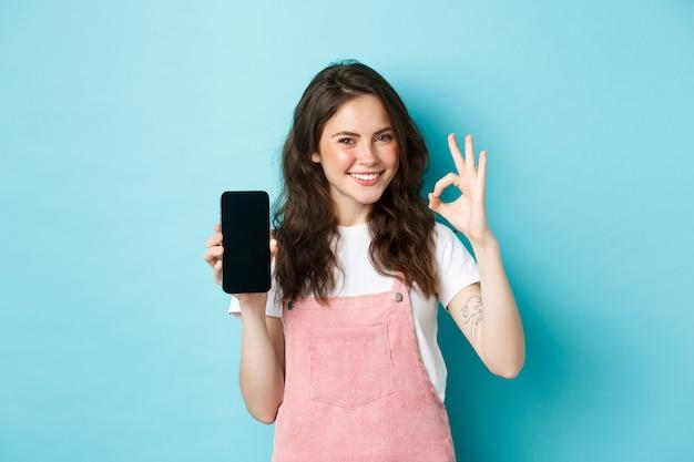 Портрет современной стильной девушки, рекомендующей интернет-магазин или мобильное приложение, показывающий знак «хорошо» с пустым экраном смартфона, одобрительный кивок, удовлетворенная улыбка, синий фон.