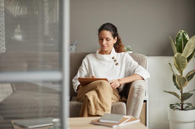 オフィス、コピースペースのソファでリラックスしながらデジタルタブレットを使用して現代の成功した実業家の肖像画