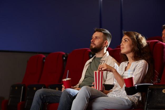 Портрет современной молодой пары в кинотеатре, смотрящей фильм и наслаждающейся попкорном, сидя на красных бархатных стульях в темной комнате, сосредоточьтесь на улыбающейся женщине на переднем плане, скопируйте пространство