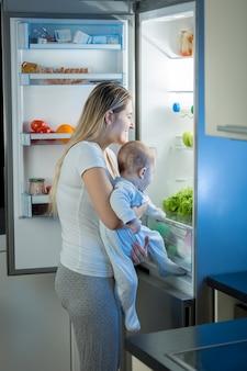 夜の冷蔵庫で何か食べるものを探している母と赤ちゃんの息子の肖像画