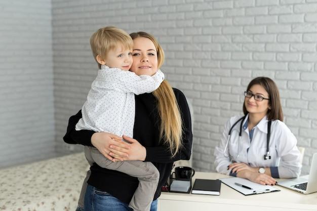 의사의 약속에서 엄마와 아이의 초상화. 병원에서 엄마와 아이를 만나는 소아과 의사.
