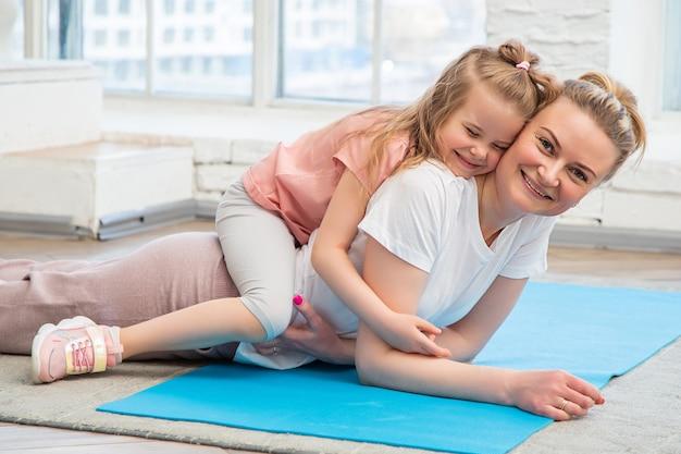 Портрет матери и дочери в спортивной одежде, лежащих на коврике для йоги перед окном, обнимающихся