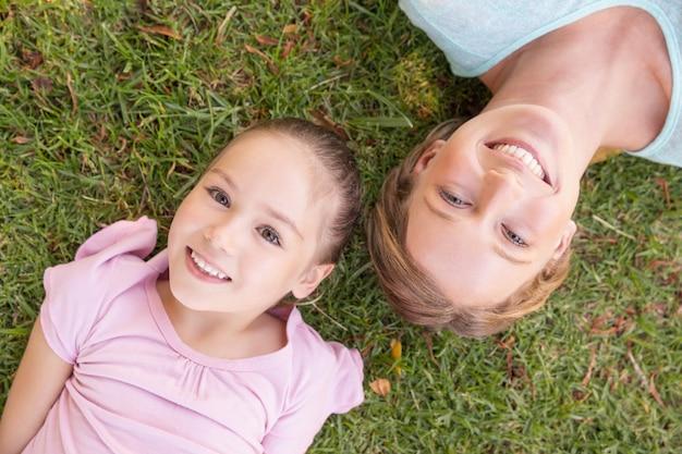 母親と娘の公園の草の上に横たわる肖像画