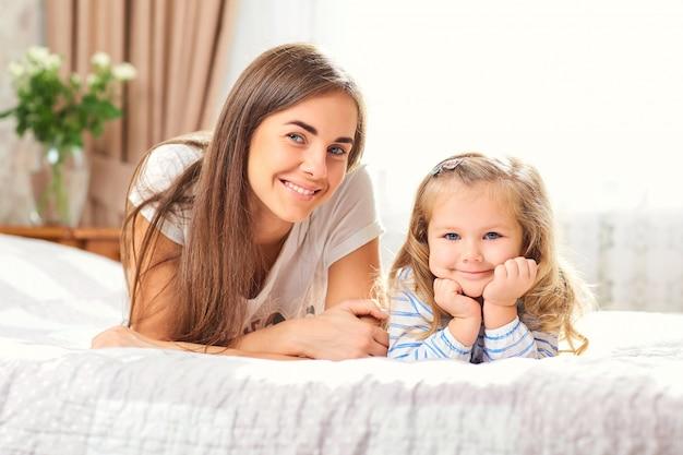 窓のそばのベッドの上の母と娘の肖像画。