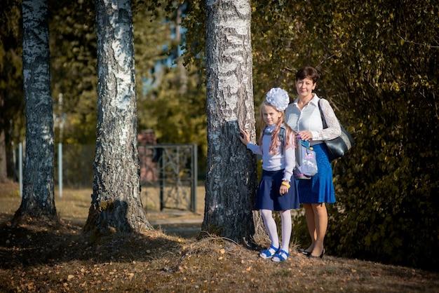 秋の公園の学校の初日の母と娘の肖像画