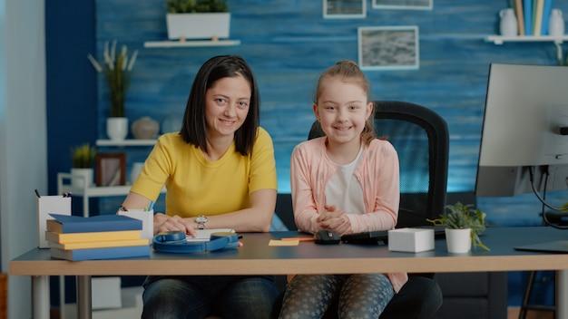 宿題のために机に座っている母と娘の肖像画