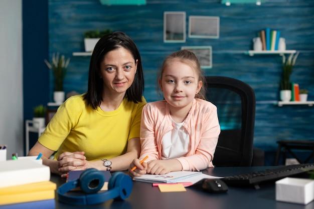 초등학교에서 온라인 수업을 기다리는 집 책상에 앉아 있는 엄마와 딸의 초상화. 인터넷에서 좋은 교육을 배우기 위해 어린 아이를 돕는 백인 성인