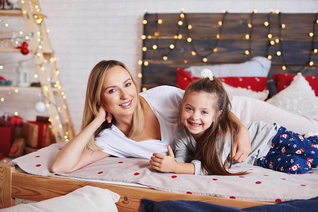 ベッドでクリスマスの朝を過ごす母と娘の肖像画