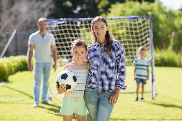 公園でサッカーと立っている母と娘の肖像